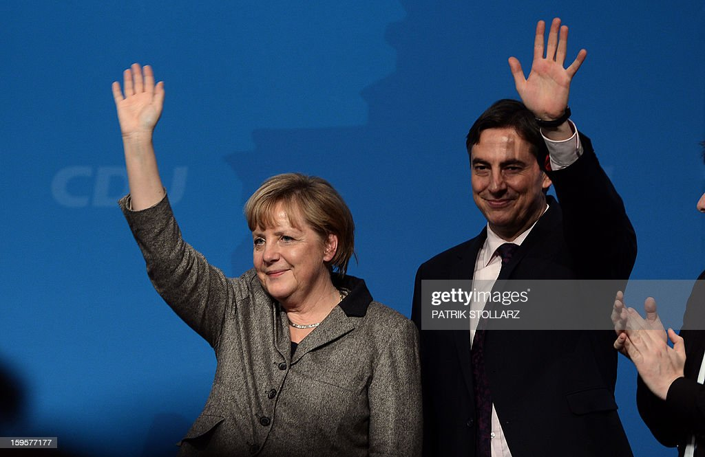 German Chancellor Angela Merkel (L) and Prime Minister of German Federal State, Lower-Saxony, David McAllister wave after a speech during an election campaign event of the regional Christian Democratic Union party for 2013 state elections in Osnabrueck, northern Germany, on January 16, 2013. McAllister started his election campaign to keep his post as Lower Saxony's State Premier after regional elections on January 20, 2013. AFP PHOTO / PATRIK STOLLARZ