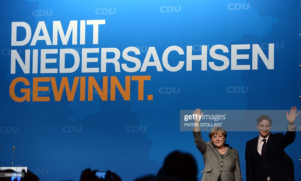 German Chancellor Angela Merkel and Prime Minister of German Federal State, Lower-Saxony, David McAllister wave after a speech in front of a placard saying 'that Lower-Saxony wins' during an election campaign event of the regional Christian Democratic Union (CDU) party for the 2013 state elections in Osnabrueck, northern Germany, on January 16, 2013.