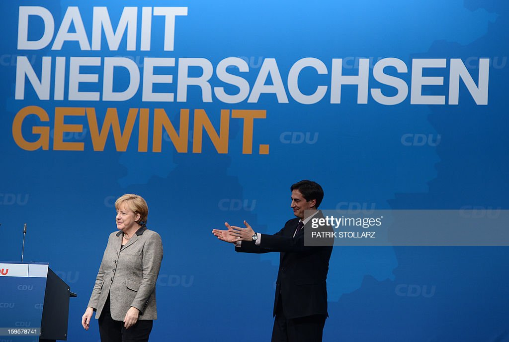 German Chancellor Angela Merkel and Prime Minister of German Federal State, Lower-Saxony, David McAllister react after a speech in front of a placard saying 'that Lower-Saxony wins' during an election campaign event of the regional Christian Democratic Union (CDU) party for the 2013 state elections in Osnabrueck, northern Germany, on January 16, 2013. AFP PHOTO / PATRIK STOLLARZ