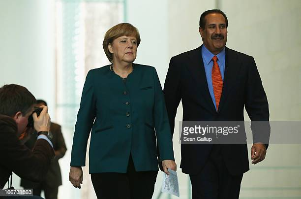 German Chancellor Angela Merkel and Qatar Prime Minister Hamad bin Jassim Al Thani arrive to speak to the media following talks at the Chancellery on...