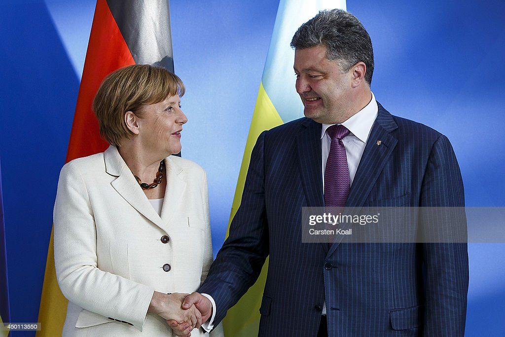 German Chancellor Angela Merkel (L) and recently-elected Ukrainian President Petro Poroshenko (R) shake hands for the media after they gave statements to the media prior to talks at the Chancellery on June 5, 2015 in Berlin, Germany. Poroshenko is meeting with western leaders as the situation in eastern Ukraine is descending further into war between government forces and Russian-backed separatists.