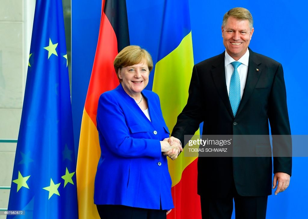 German Chancellor Angela Merkel and Romanian President Klaus Iohannis shake hands after a news conference after talks in Berlin on June 19, 2017. /