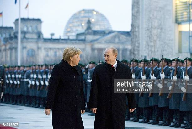 German Chancellor Angela Merkel and Russian Prime Minister Vladimir Putin review an honour guard during an official welcoming ceremony at the...