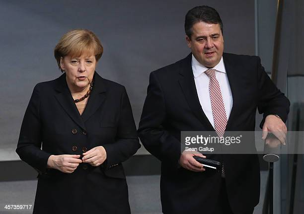 German Chancellor Angela Merkel and Sigmar Gabriel who will become Germany's new Vice Chancellor and Economy and Energy Minister chat during a vote...