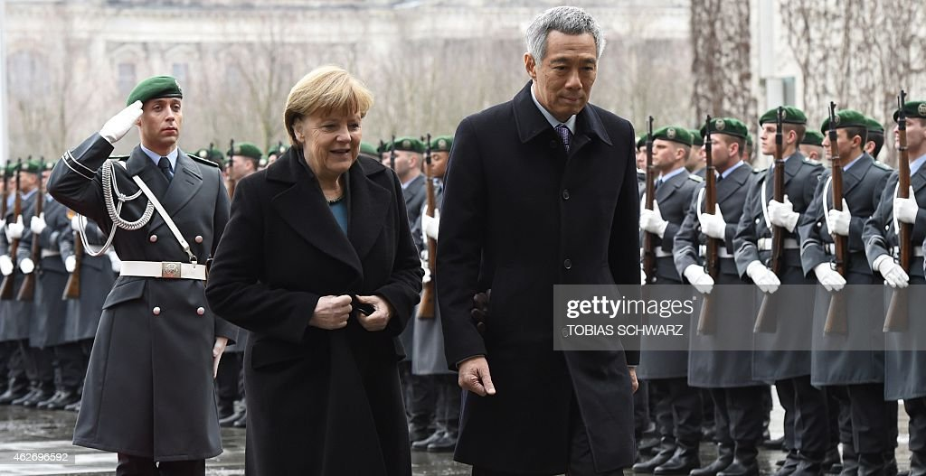 German Chancellor Angela Merkel and Singapore's Prime Minister Lee Hsien Loong inspect the guard of honour during a welcome ceremony before talks at...