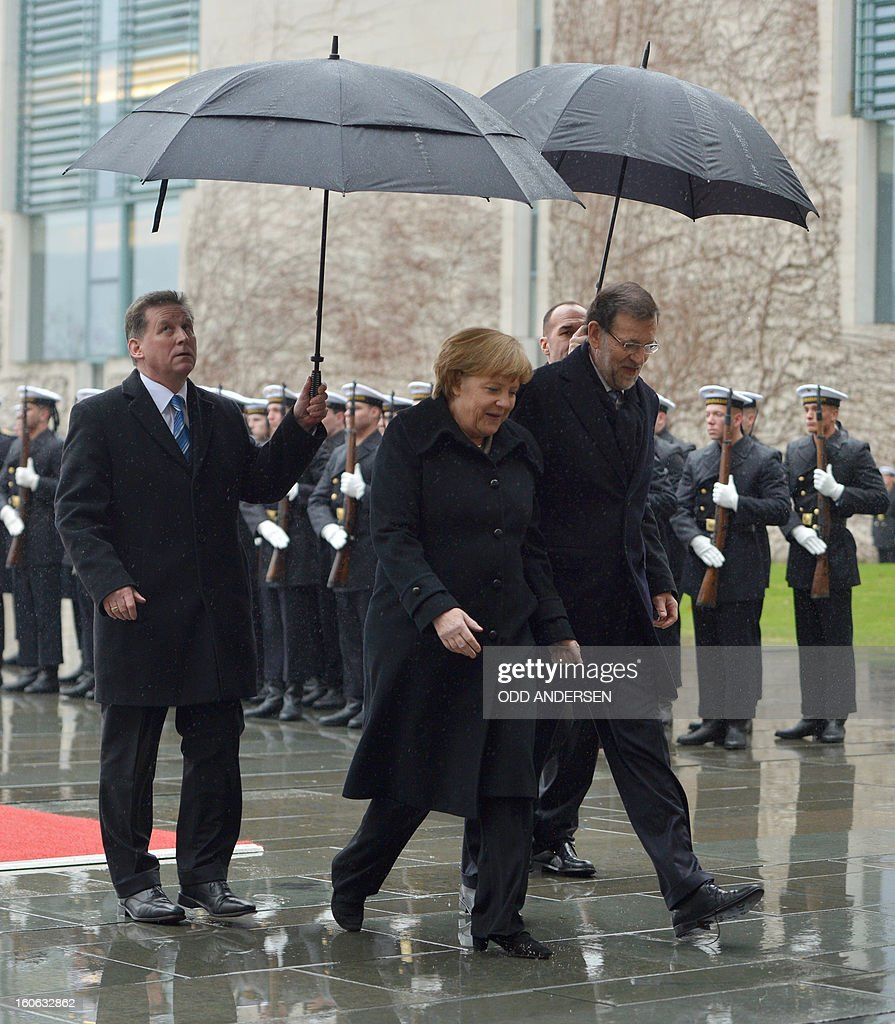 German Chancellor Angela Merkel and Spain's Prime Minister Mariano Rajoy (R) inspect an honor guard upon his arrival at the Chancellery in Berlin on February 4, 2013 before their meeting. Merkel hosts for talks Rajoy, currently under fire for alleged corruption.