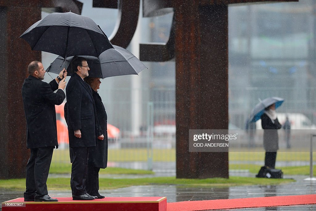 German Chancellor Angela Merkel (R) and Spain's Prime Minister Mariano Rajoy listen to their national anthem at the Chancellery in Berlin on February 4, 2013 before their meeting. Merkel hosts for talks Rajoy, currently under fire for alleged corruption.