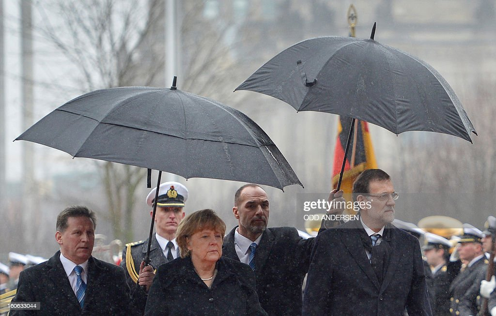 German Chancellor Angela Merkel and Spain's Prime Minister Mariano Rajoy (R) inspect an honor guard upon his arrival at the Chancellery in Berlin on February 4, 2013 before their meeting. Merkel hosts for talks Rajoy, currently under fire for alleged corruption. AFP PHOTO / ODD ANDERSEN