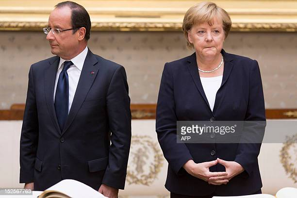 German Chancellor Angela Merkel and the French president Francois Hollande wait to sign their names in the Golden Book at the ceremony on the...