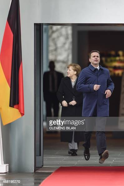 German Chancellor Angela Merkel and the Head of the German governmental press and informationagency Steffen Seibert wait for French President...