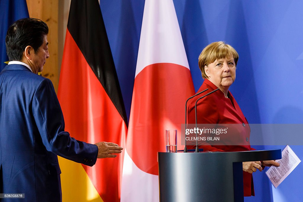 German Chancellor Angela Merkel and the Japanese Prime Minister Shinzo Abe arrive for a press conference after bilateral talks at the state guest house 'Schloss Meseberg' in Gransee in Brandenburg near Berlin, on May 4, 2016. / AFP / CLEMENS