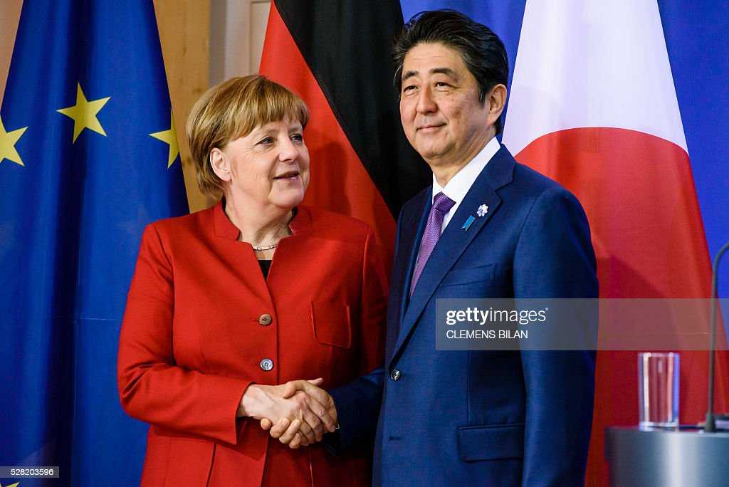 German Chancellor Angela Merkel and the Japanese Prime Minister Shinzo Abe shake hands after bilateral talks at the state guest house 'Schloss Meseberg' in Gransee in Brandenburg near Berlin, on May 4, 2016. / AFP / CLEMENS