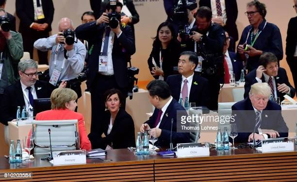 German Chancellor Angela Merkel and the President of China Xi Jinping look to the photographers while US President Donald Trump looks down before...