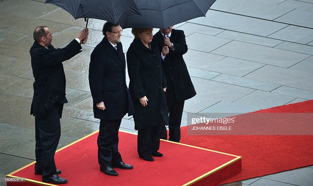 German Chancellor Angela Merkel (2nd R) and the Spanish Prime Minister Mariano Rajoy (2nd L) inspect a military honor guard at the Chancellery in Berlin on February 4, 2013.