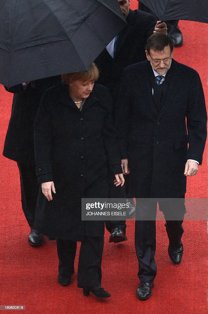 German Chancellor Angela Merkel (L) and the Spanish Prime Minister Mariano Rajoy (R) inspect a military honor guard at the Chancellery in Berlin on February 4, 2013.
