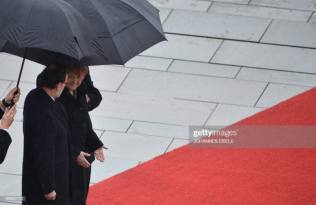 German Chancellor Angela Merkel (R) and the Spanish Prime Minister Mariano Rajoy (L) inspect a military honor guard at the Chancellery in Berlin on February 4, 2013.