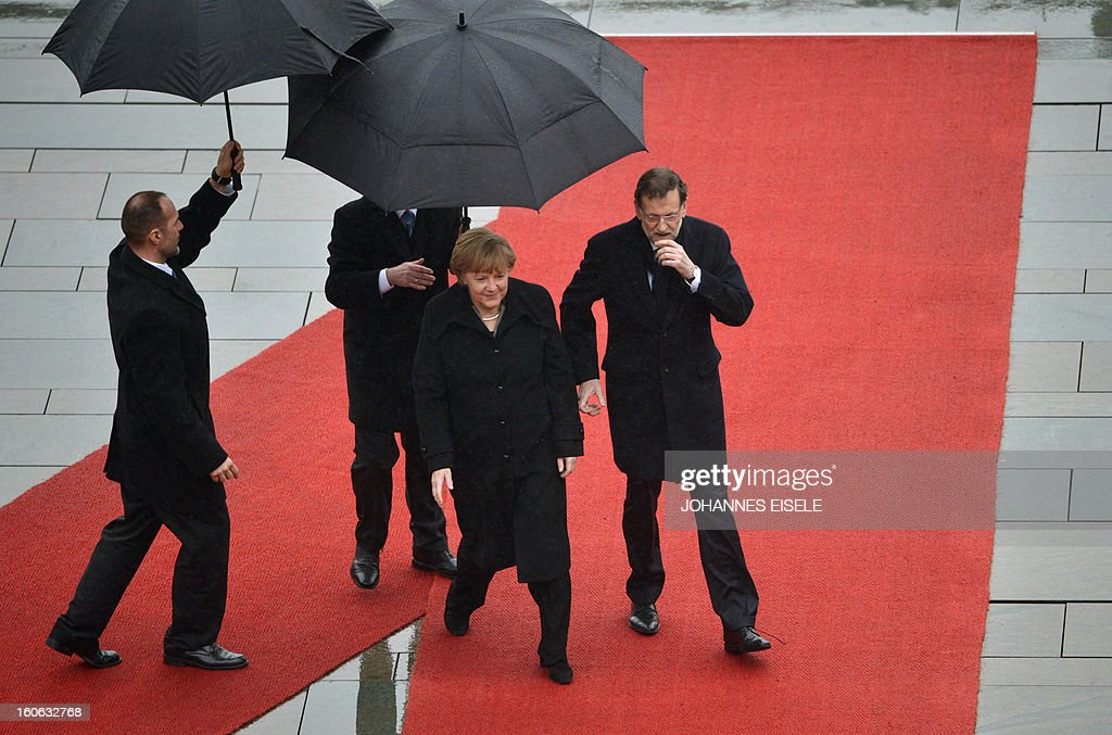 German Chancellor Angela Merkel (C) and the Spanish Prime Minister Mariano Rajoy (R) inspect a military honor guard at the Chancellery in Berlin on February 4, 2013.