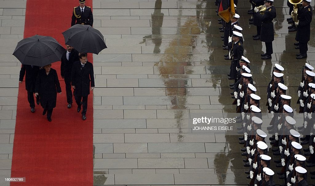 German Chancellor Angela Merkel (L) and the Spanish Prime Minister Mariano Rajoy (2nd L) inspect a military honor guard at the Chancellery in Berlin on February 4, 2013. AFP PHOTO / JOHANNES EISELE