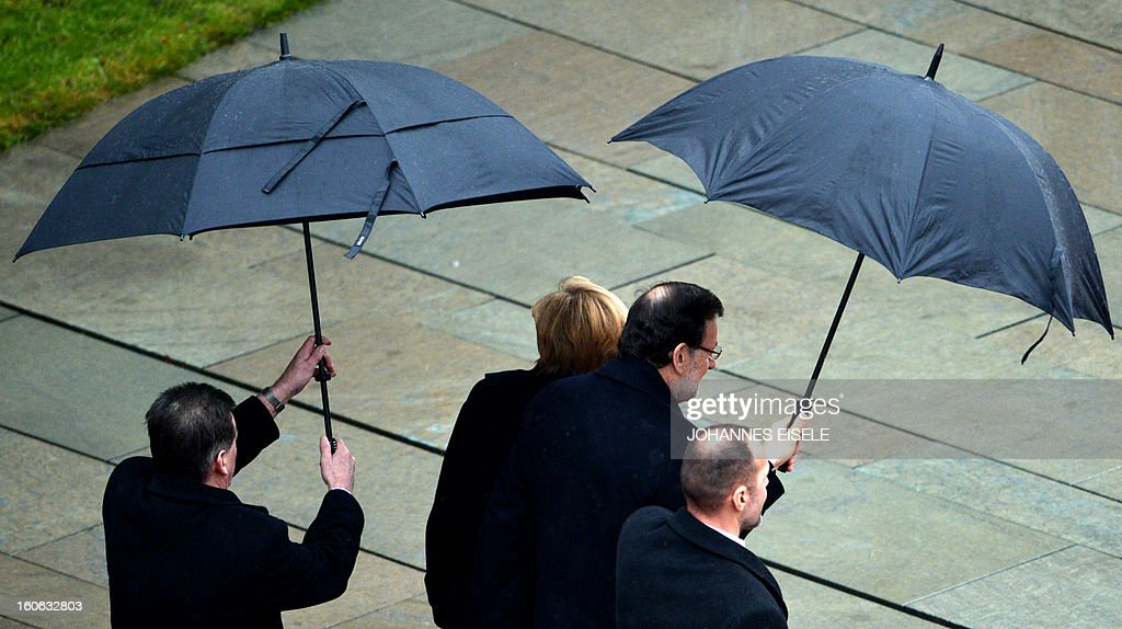 German Chancellor Angela Merkel (2nd L) and the Spanish Prime Minister Mariano Rajoy (2nd R) inspect a military honor guard at the Chancellery in Berlin on February 4, 2013.