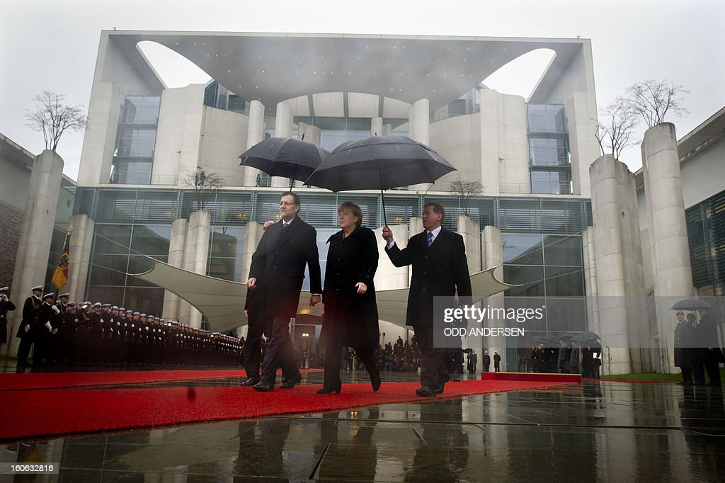 German Chancellor Angela Merkel (C) and the Spanish Prime Minister Mariano Rajoy (L) inspect a military honor guard at the Chancellery in Berlin on February 4, 2013.