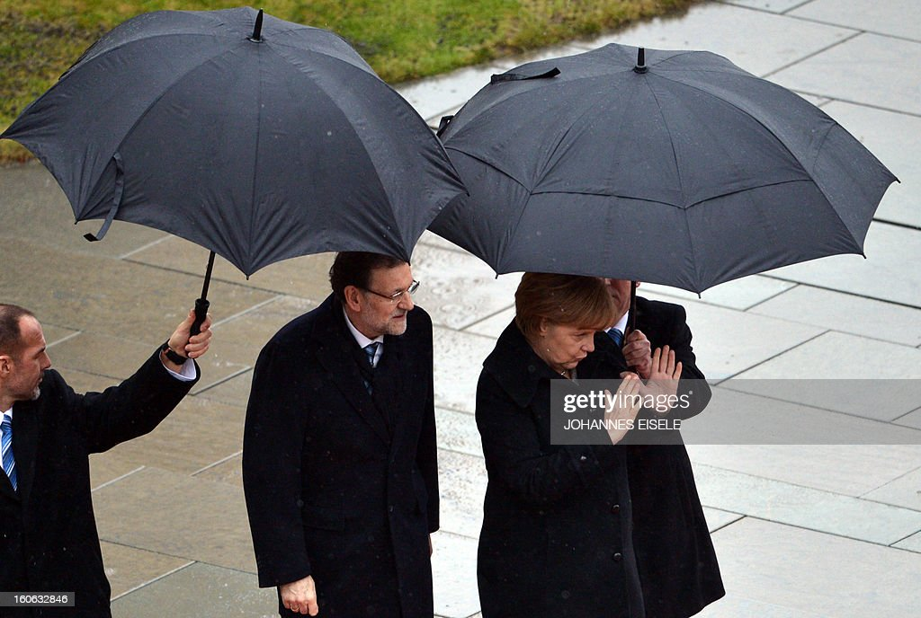 German Chancellor Angela Merkel (2nd R) and the Spanish Prime Minister Mariano Rajoy (2nd L) inspect a military honor guard at the Chancellery in Berlin on February 4, 2013. AFP PHOTO / JOHANNES EISELE