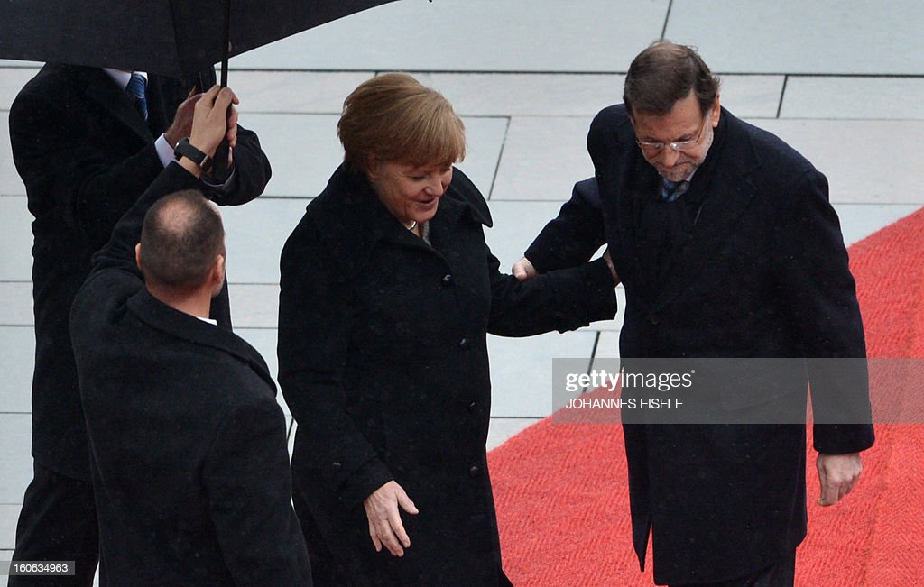 German Chancellor Angela Merkel (2nd R) and the Spanish Prime Minister Mariano Rajoy (R) inspect a military honor guard at the Chancellery in Berlin on February 4, 2013.