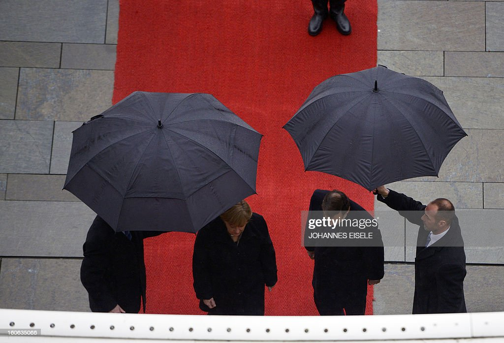 German Chancellor Angela Merkel (2nd L) and the Spanish Prime Minister Mariano Rajoy (2nd R) are sheltered from the rain under umbrellas as they inspected a military honor guard at the Chancellery in Berlin on February 4, 2013. AFP PHOTO / JOHANNES EISELE