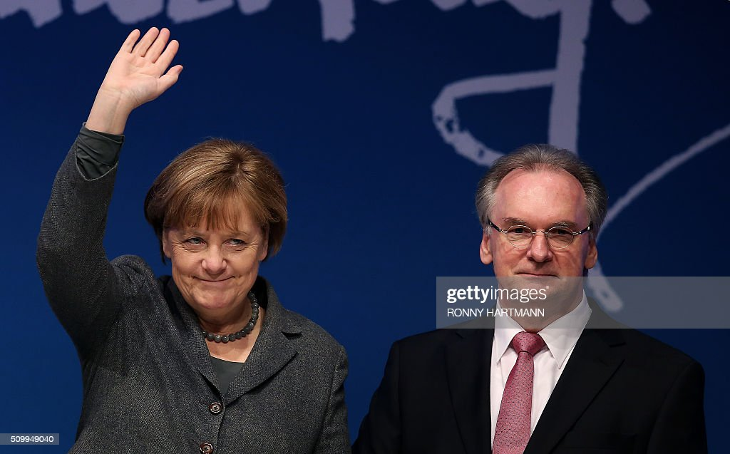 German Chancellor Angela Merkel (L) and the State Premier of the federal state of Saxony-Anhalt, Reiner Haseloff, launch the election campaign of their Christian Democratic Union (CDU) party for state elections in Magdeburg, eastern Germany, on February 13, 2016. Regional elections in three German federal states - Saxony-Anhalt, Rhineland Palatinate and Baden-Wuerttemberg - will take place on March 13, 2016. / AFP / Ronny Hartmann