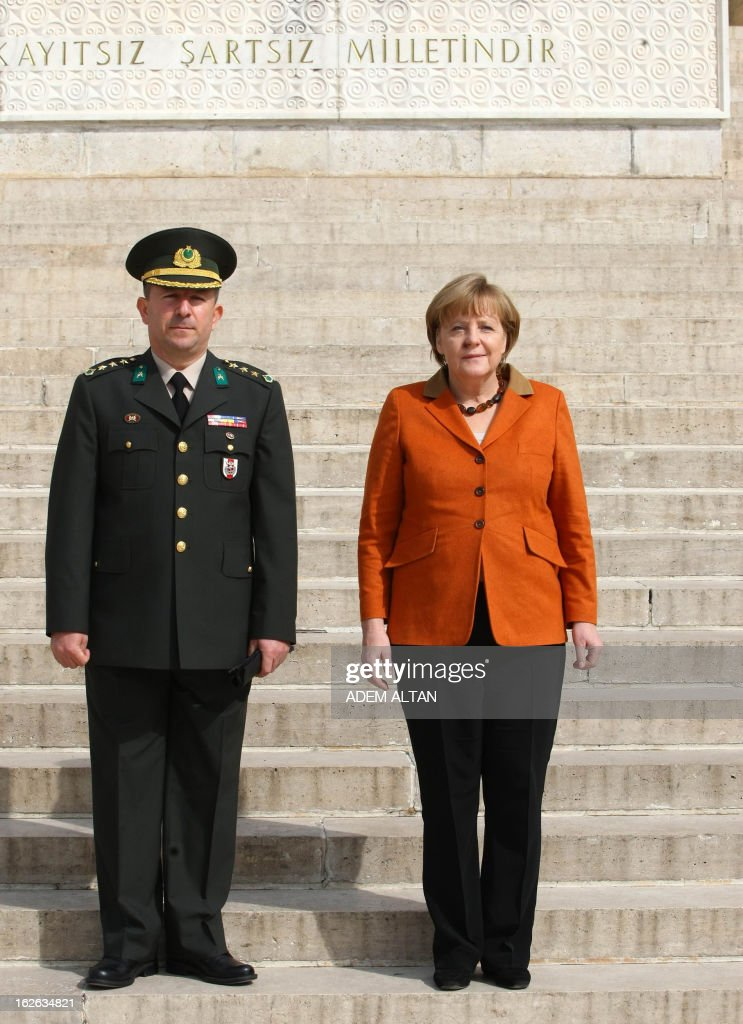 German Chancellor Angela Merkel (R) and Turkish army col. Muzaffer Taytak pose in front of the mausoleum of Turkey's Republic's founder Kemal Ataturk in Ankara, on February 25, 2013, on the second an final day of her official visit to Turkey. AFP PHOTO ADEM ALTAN