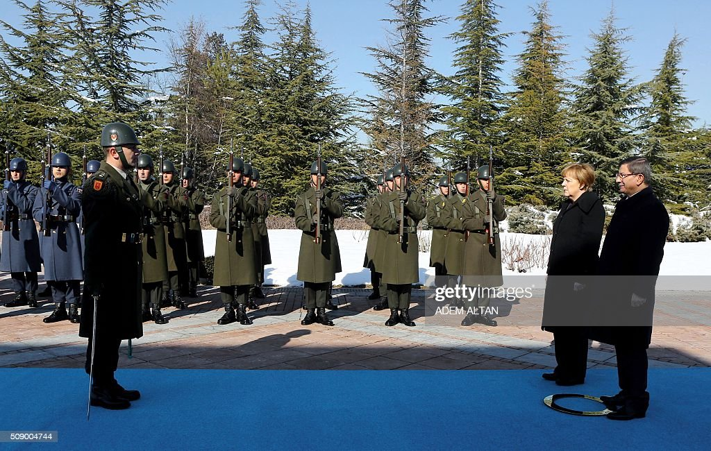 German Chancellor Angela Merkel (2nd R) and Turkish Prime Minister Ahmet Davutoglu review a military honour guard in Ankara on February 8, 2016. Merkel is to hold talks with Turkey's President Recep Tayyip Erdogan and Prime Minister Ahmet Davutoglu to press Turkey to strengthen border controls to stem the flow of migrants and refugees heading for Europe. / AFP / ADEM ALTAN