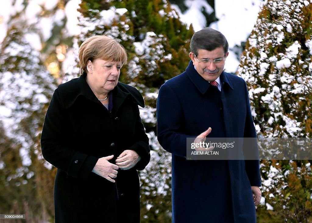 German Chancellor Angela Merkel (L) and Turkish Prime Minister Ahmet Davutoglu speak after a welcoming ceremony in Ankara on February 8, 2016. Merkel is to hold talks with Turkey's President Recep Tayyip Erdogan and Prime Minister Ahmet Davutoglu to press Turkey to strengthen border controls to stem the flow of migrants and refugees heading for Europe. / AFP / ADEM ALTAN