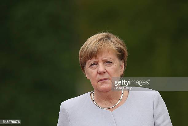 German Chancellor Angela Merkel and Ukrainian Prime Minister Volodymyr Groysman prepare to listen to their countries' national anthems upon...