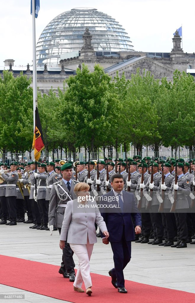 German chancellor Angela Merkel (L) and Ukraininian Prime Minister Volodymyr Groysman review a guard of honour before talks at the chancellery in Berlin on June 27, 2016. / AFP / John MACDOUGALL