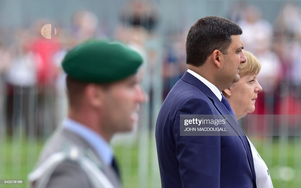 German chancellor Angela Merkel (R) and Ukraininian Prime Minister Volodymyr Groysman listen to their national anthems during a welcoming ceremony before talks at the chancellery in Berlin on June 27, 2016. / AFP / John MACDOUGALL