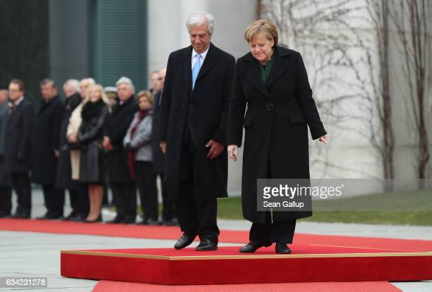 German Chancellor Angela Merkel and Uruguayan President Tabare Vazquez descend from a podium after listening to their countries' national anthems...