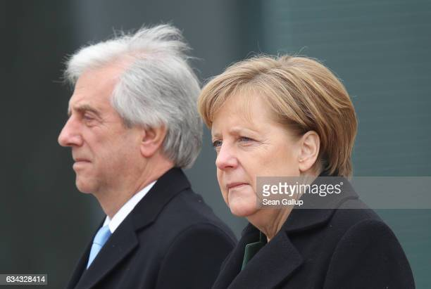 German Chancellor Angela Merkel and Uruguayan President Tabare Vazquez listen to their countries' national anthems upon Vazquez's arrival at the...