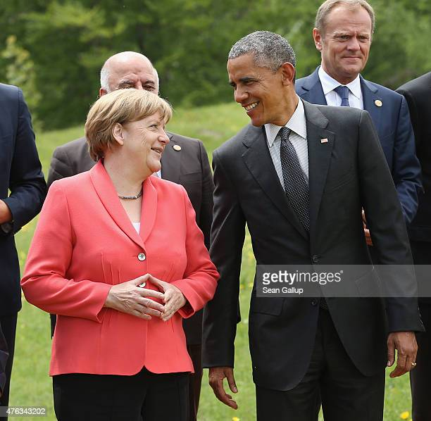 German Chancellor Angela Merkel and US President Barack Obama chat during the Outreach group photo on the second day of the summit of G7 nations at...