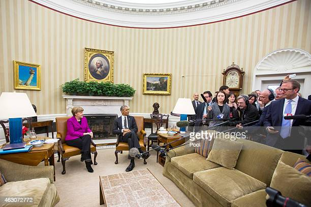 German Chancellor Angela Merkel AND US President Barack Obama pose during a photo op before their meeting as the press looks on in the Oval Office of...