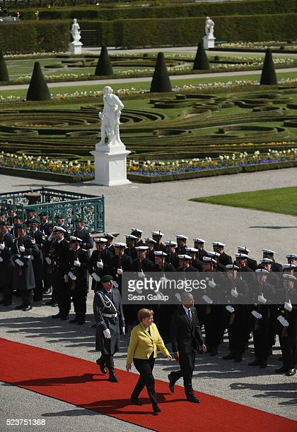 German Chancellor Angela Merkel and US President Barack Obama review a guard of honour at Schloss Herrenhausen palace upon Obama's arrival on April...