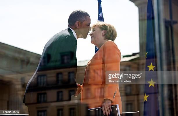 German Chancellor Angela Merkel and US President Barack Obama shake hands in front of Berlin's landmark the Brandenburg Gate near the US embassy on...