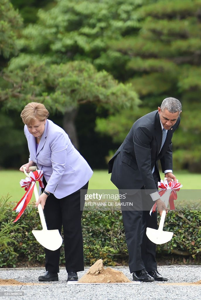 German Chancellor Angela Merkel and US President Barack Obama take part in a tree planting ceremony on the grounds of the Ise-Jingu Shrine in the city of Ise, in Mie prefecture on May 26, 2016 on the first day of the G7 leaders summit. World leaders kick off two days of G7 talks in Japan on May 26 with the creaky global economy, terrorism, refugees, China's controversial maritime claims, and a possible Brexit headlining their packed agenda. / AFP / STEPHANE