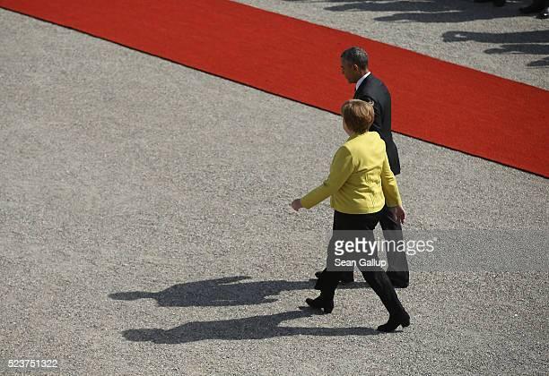 German Chancellor Angela Merkel and US President Barack Obama walk walk outside at Schloss Herrenhausen palace upon Obama's arrival on April 24 2016...