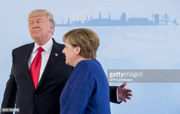 TOPSHOT German Chancellor Angela Merkel and US President Donald Trump leave for a bilateral meeting on the eve of the G20 summit in Hamburg northern...
