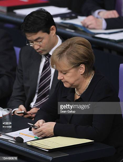 German Chancellor Angela Merkel and Vice Chancellor and Economy Minister Philipp Roesler type messages on their smartphones during debates at the...