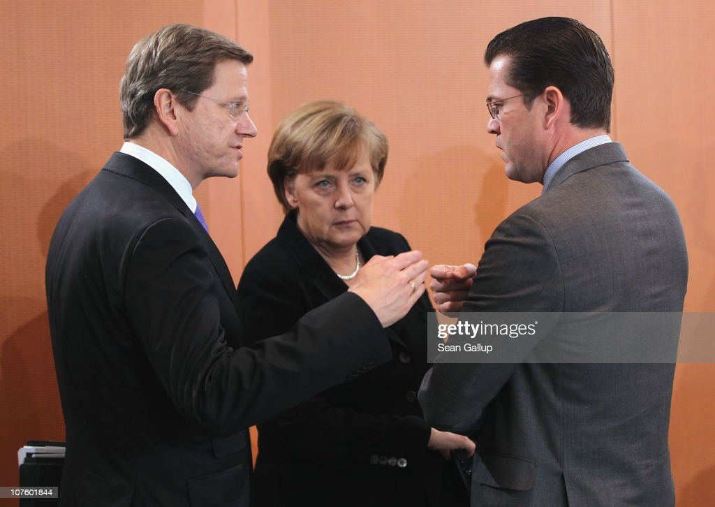 German Chancellor <a gi-track='captionPersonalityLinkClicked' href=/galleries/search?phrase=Angela+Merkel&family=editorial&specificpeople=202161 ng-click='$event.stopPropagation()'>Angela Merkel</a> (C) and Vice Chancellor and Foreign Minister <a gi-track='captionPersonalityLinkClicked' href=/galleries/search?phrase=Guido+Westerwelle&family=editorial&specificpeople=208748 ng-click='$event.stopPropagation()'>Guido Westerwelle</a> (L) chat with Defense Minister <a gi-track='captionPersonalityLinkClicked' href=/galleries/search?phrase=Karl-Theodor+zu+Guttenberg&family=editorial&specificpeople=5585450 ng-click='$event.stopPropagation()'>Karl-Theodor zu Guttenberg</a> upon their arrival for the weekly German government cabinet meeting at the Chancellery (Bundeskanzleramt) on December 15, 2010 in Berlin, Germany. Zu Guttenberg is coming under intense criticism following his decision to allow both his wife Stephanie and talk show host Johannes B. Kerner to accompany him on a recent visit to German ISAF troops in Afghanistan.