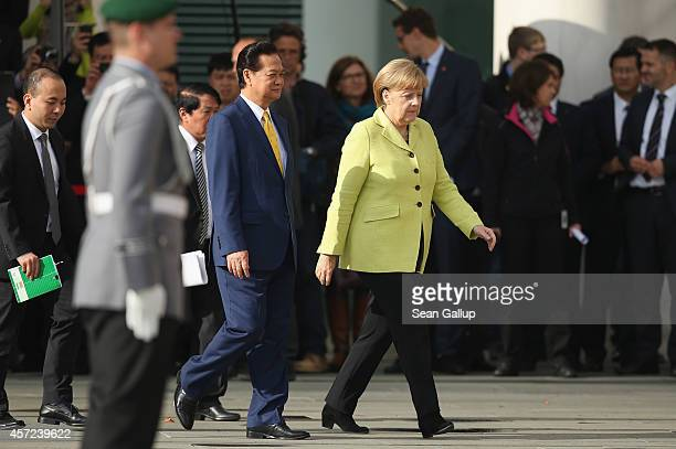 German Chancellor Angela Merkel and Vietnamese Prime Minister Nguyen Tan Dung prepare to review a guard of honour upon his arrival for talks at the...