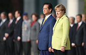 German Chancellor Angela Merkel and Vietnamese Prime Minister Nguyen Tan Dung listen to their countries' respective national anthems upon his arrival...