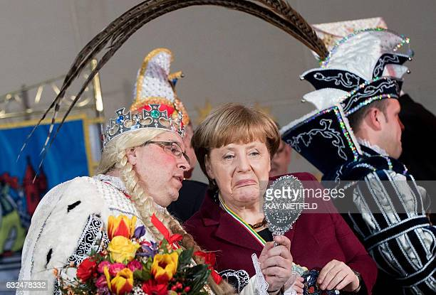 German Chancellor Angela Merkel and virgin Sandra of the Carneval Association of the city of Homburg representing the federal state of Hesse react as...