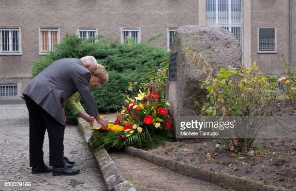 German Chancellor Angela Merkel and with former Prisoner Arno Defke lay a wreath while she visits the former prison of the East German communistera...