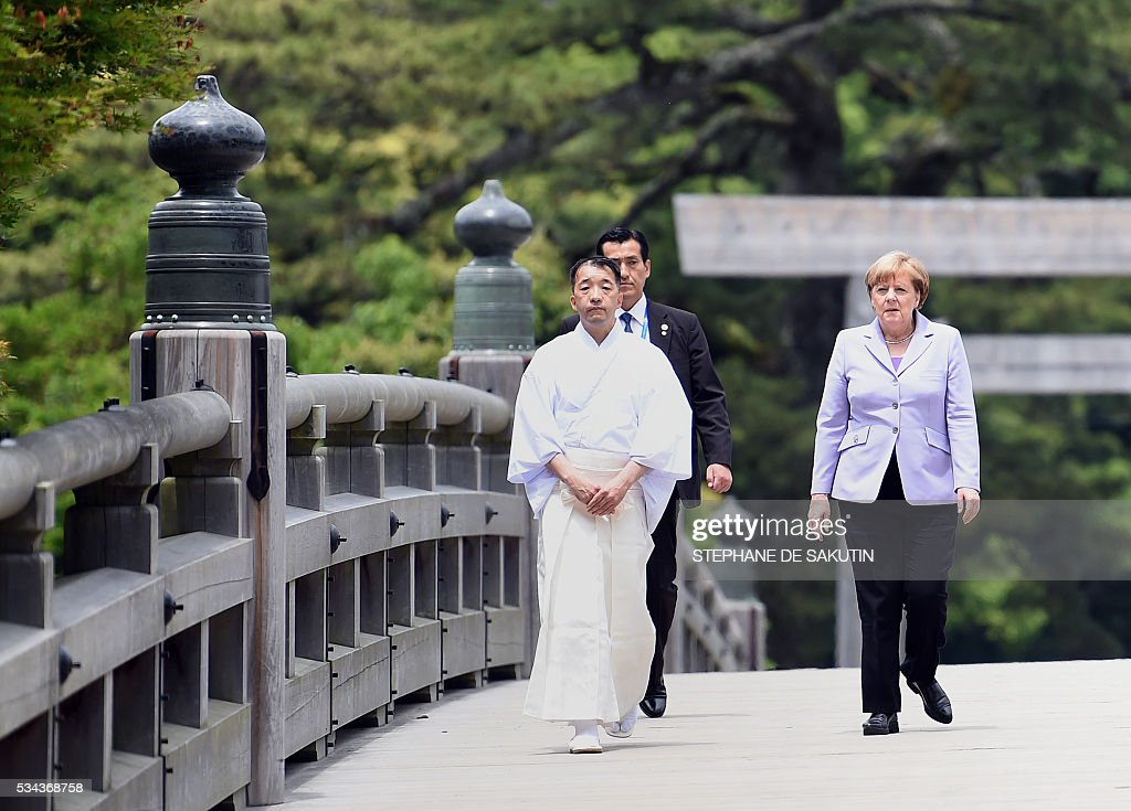 German Chancellor Angela Merkel (R) arrives at Ise-Jingu Shrine in the city of Ise in Mie prefecture, on May 26, 2016, on the first day of the G7 leaders summit. World leaders kick off two days of G7 talks in Japan on May 26 with the creaky global economy, terrorism, refugees, China's controversial maritime claims, and a possible Brexit headlining their packed agenda. / AFP / STEPHANE